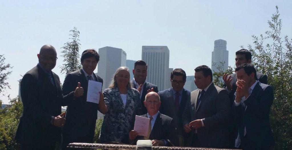 Gov. Brown signs Senate Bill 32 into law. Present are (from left) Asm Jones-Sawyer, Sen/Speaker de Leon, Sen Pavley, Sen Lara, Asm Gomez, Asm Garcia, Asm Dababneh, and Asm/Speaker Rendon